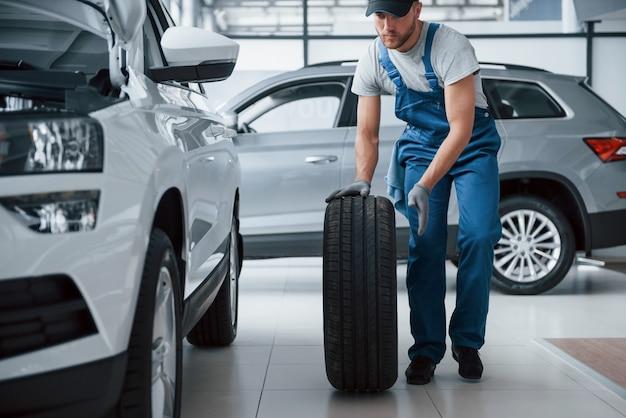 Nada demais. mecânico segurando um pneu na oficina. substituição de pneus de inverno e verão