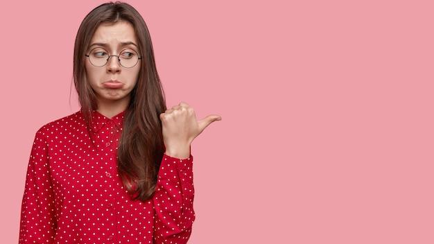 Nada impressionante aí. mulher triste e ofensiva franze os lábios, aponta para a direita com o polegar, vestida elegantemente, fica de pé sobre a parede rosa