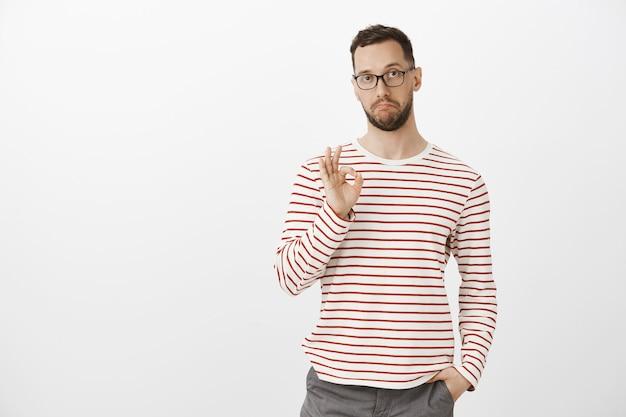 Nada mal, como sua ideia, bom trabalho. satisfeito e impressionado cara atraente de óculos e roupas listradas