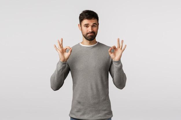 Nada mal, muito bem. marido barbudo adulto julgador satisfeito de suéter cinza concorda com você, mostra bem, gesto de confirmação ok e sorridente, classifica o produto normal, recomenda