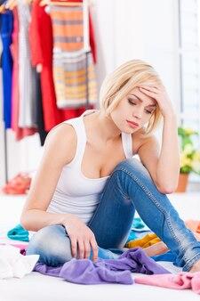 Nada para vestir! mulher loira jovem deprimida sentada na cama com as roupas ao redor e olhando para longe