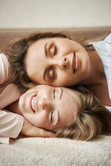 Nada poderia separar ou quebrar essa amizade. tiro vertical de mãe fofa deitado na cabeça da filha, sorrindo amplamente, sentindo a unidade e relaxando no fim de semana, tendo conversas íntimas sobre a vida