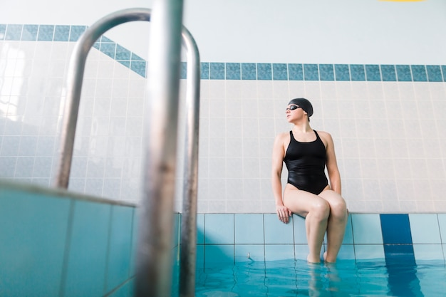 Nadador apto que senta-se no lado da piscina
