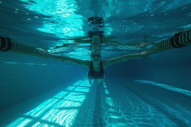 Nadador atlético nadando em direção a câmera