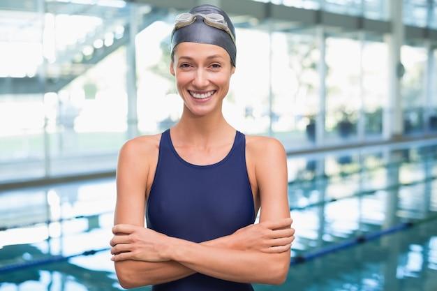Nadador bonito sorrindo para a câmera à beira da piscina