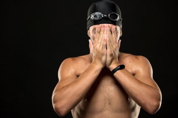 Nadador com tiro médio com as palmas das mãos no rosto