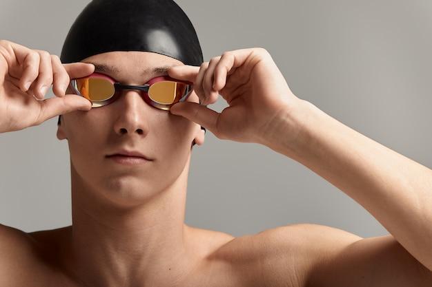 Nadador de boné e máscara, sobre fundo cinza, preparando-se para nadar, close-up, banner publicitário para piscinas, espaço de cópia