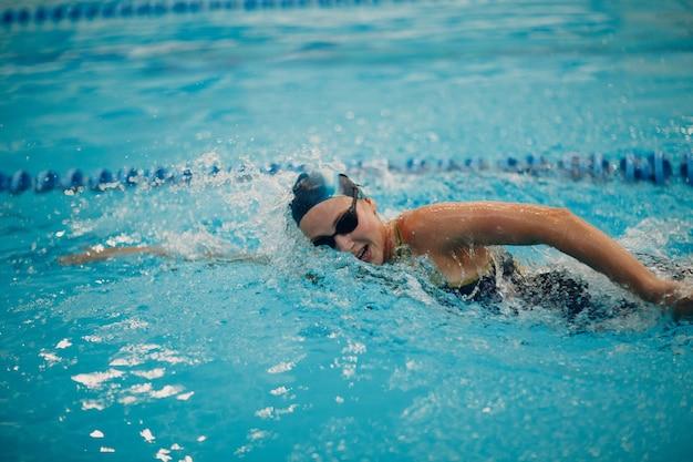 Nadador de jovem nada na piscina.