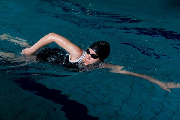 Nadador de tiro médio com óculos de proteção na piscina