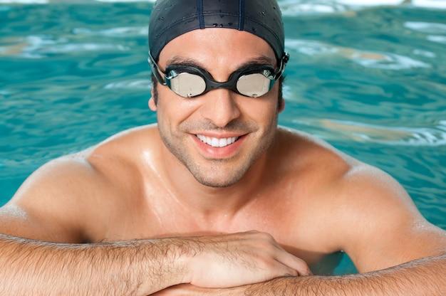 Nadador feliz e sorridente usando óculos e boné na piscina