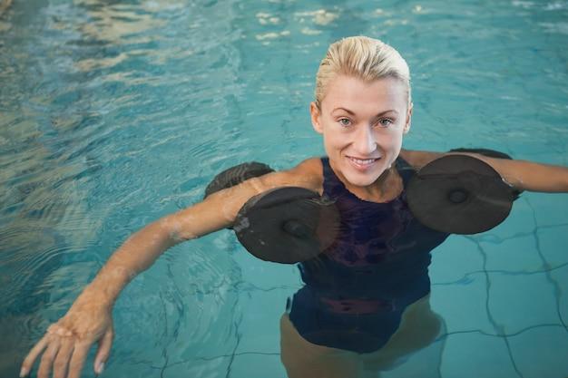 Nadador feminino malhar com halteres de espuma na piscina