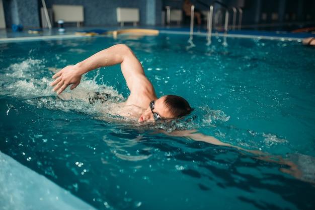 Nadador masculino em óculos nada no treino na piscina. treinamento de esportes aquáticos, estilo de vida saudável