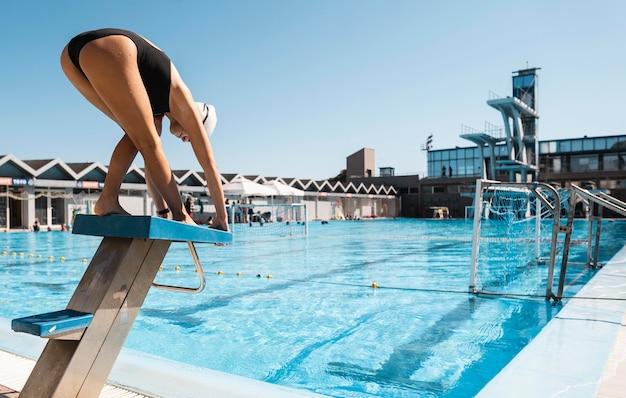 Nadador profissional pronto para pular na piscina