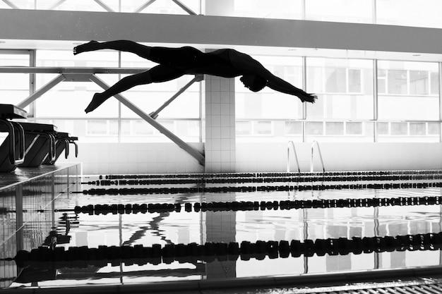 Nadador pulando na piscina
