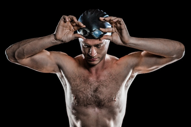Nadador segurando óculos de natação