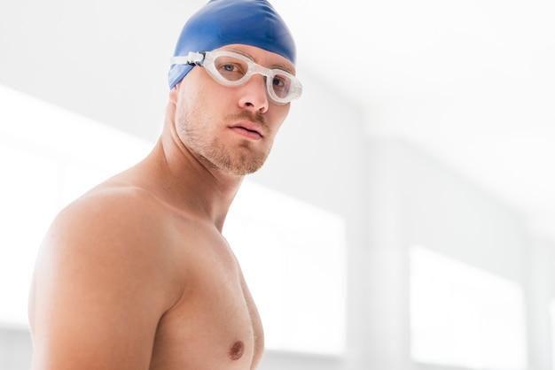 Nadador sério de baixo ângulo com óculos de proteção