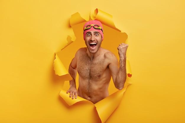 Nadador triunfante comemora vitória, ergue o punho cerrado, grita alto, tem corpo nu