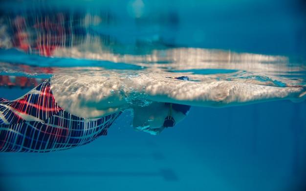 Nadadora em traje de banho, boné e óculos a nadar na piscina, vista subaquática