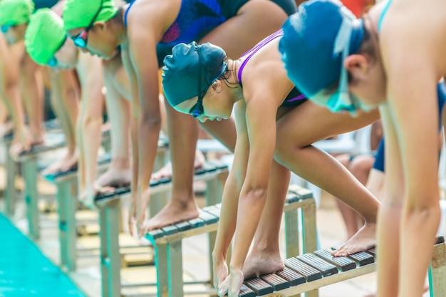 Nadadoras se preparam e esperam a sua vez de nadar em uma piscina local