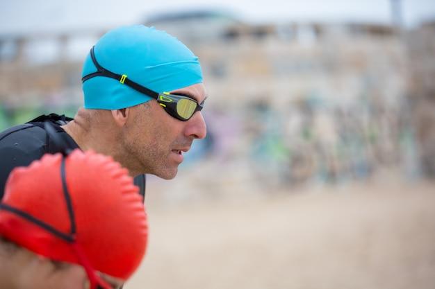Nadadores em roupas de mergulho na praia