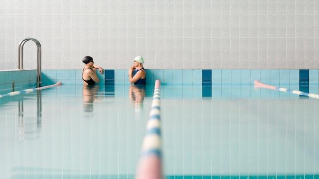 Nadadores relaxantes na piscina coberta