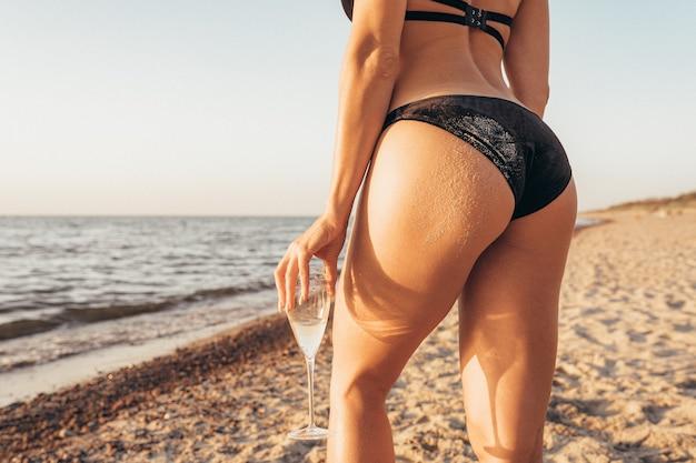 Nádega de mulher suja com areia, ficar na praia ao pôr do sol com um copo de vinho.