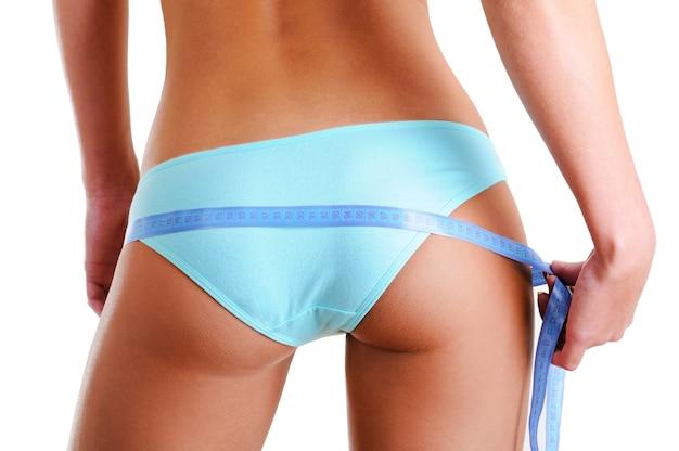 Nádegas femininas com fita métrica. visão traseira. isolado no branco. foto de close-up.