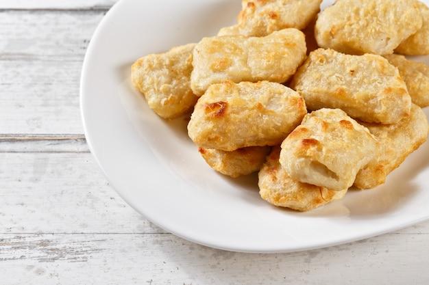 Naggets de frango. pepitas fritas fatias de frango na mesa de madeira