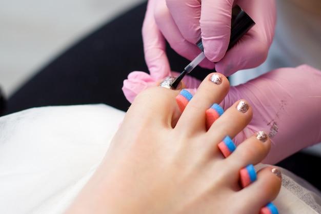 Nail care and pedicure concept. as mãos do manicuro do close up em luvas cor-de-rosa estão pintando o verniz para as unhas do ouro nos dedos do pé do cliente.