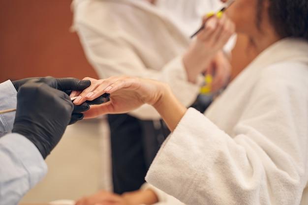 Nail master qualificado usando um bastão de madeira ao trabalhar com as cutículas do cliente durante o procedimento de maquiagem