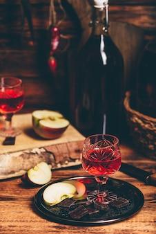 Nalivka de groselha vermelha caseira e chocolate com fatias de maçã na bandeja de metal