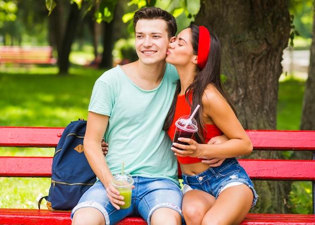 Namorada beijando seu namorado segurando smoothies em copo de plástico