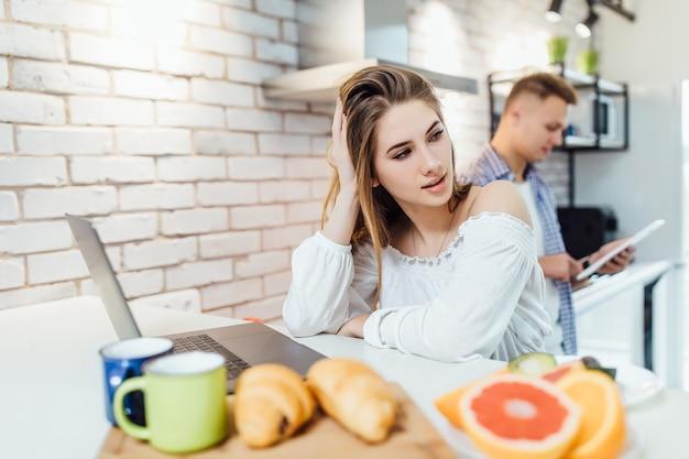 Namorada bonita trabalhando no laptop enquanto o homem procura a receita para o jantar. família na cozinha ..