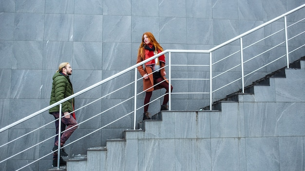 Namorada e namorado na moda sobem as escadas da rua