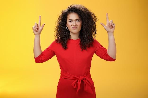 Namorada mal-humorada e insatisfeita com penteado encaracolado em um vestido vermelho elegante, levantando as mãos apontando para cima e fazendo uma careta insatisfeita e enojada, expressando aversão e aversão pela parede amarela.