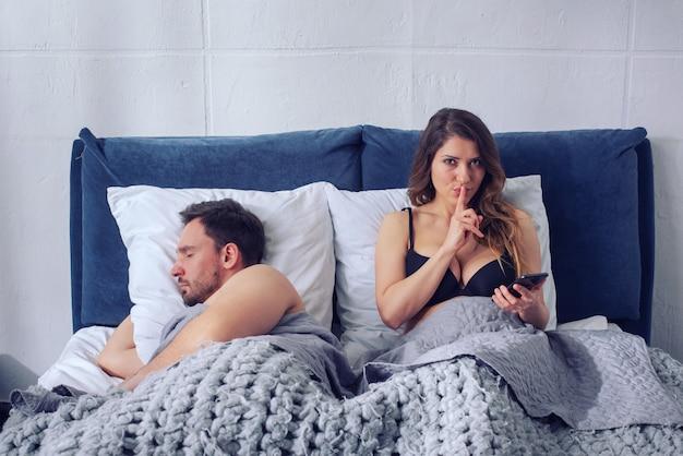 Namorada secretamente conversando com os outros enquanto ele dorme. conceito de infidelidade