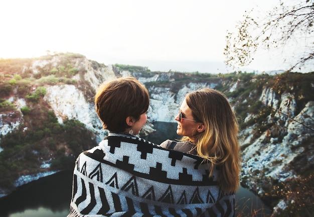 Namoradas abraçar juntos sob o cobertor no topo da montanha