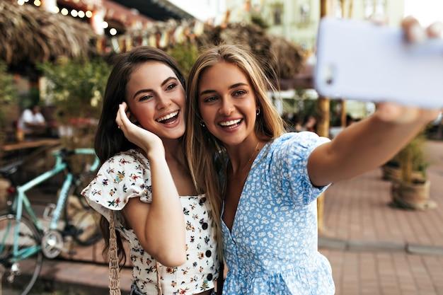 Namoradas alegres e de ótimo humor tiram selfie ao ar livre e sorriem