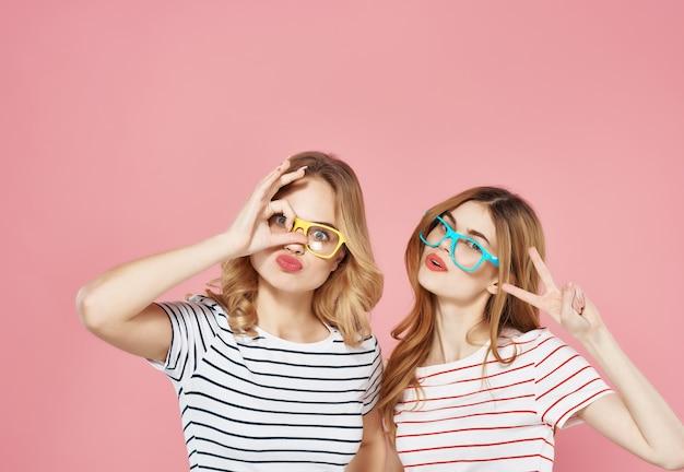 Namoradas alegres e elegantes em camiseta listrada posando com fundo rosa