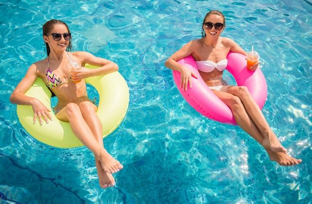 Namoradas alegres estão se divertindo na piscina.