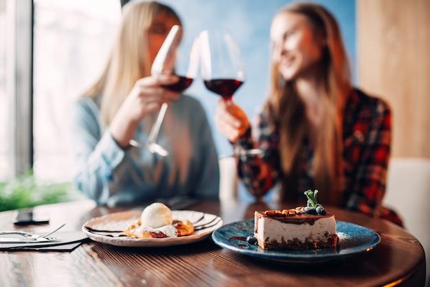 Namoradas bebem vinho tinto e comem sobremesa no restaurante. bolo de chocolate e álcool na mesa