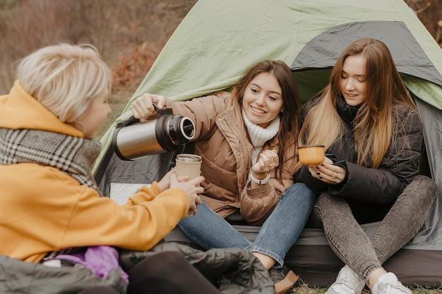Namoradas, bebendo chá na barraca