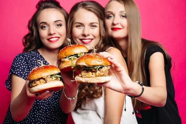 Namoradas bonitas com hambúrgueres suculentos.