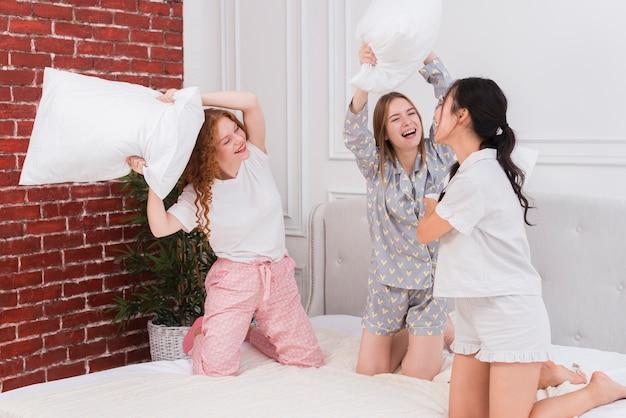 Namoradas brincalhões lutando com travesseiros