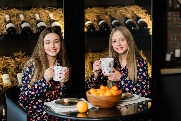 Namoradas celebrando a véspera de ano novo e o natal e comendo tangerinas na cama. existem presentes e ramos de abeto decorados com bolas douradas.