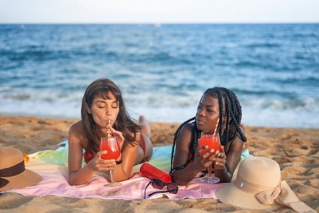 Namoradas com coquetéis descansando na praia