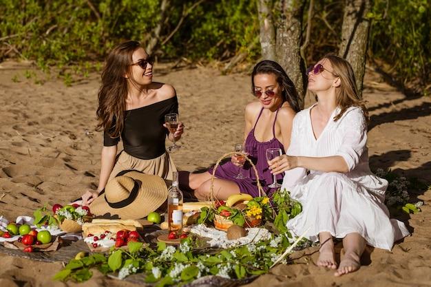 Namoradas comemoram no verão em um piquenique. mulheres bonitas estão se divertindo com álcool na natureza. garotas caucasianas se divertem na natureza na costa, sentadas em um cobertor, bebem vinho e comem frutas
