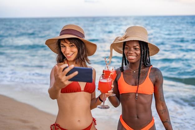 Namoradas contentes com bebidas fazendo selfie na praia