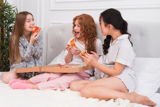 Namoradas de alto ângulo comendo pizza