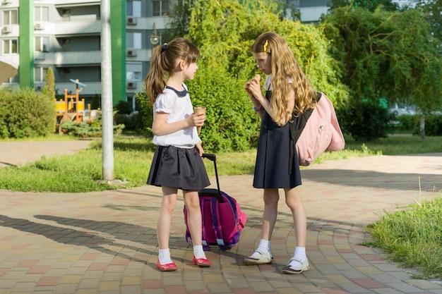 Namoradas de colegial com mochilas comendo sorvete